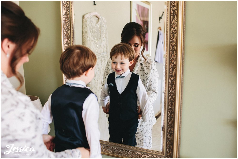 boy looks in mirror wearing his wedding outfit