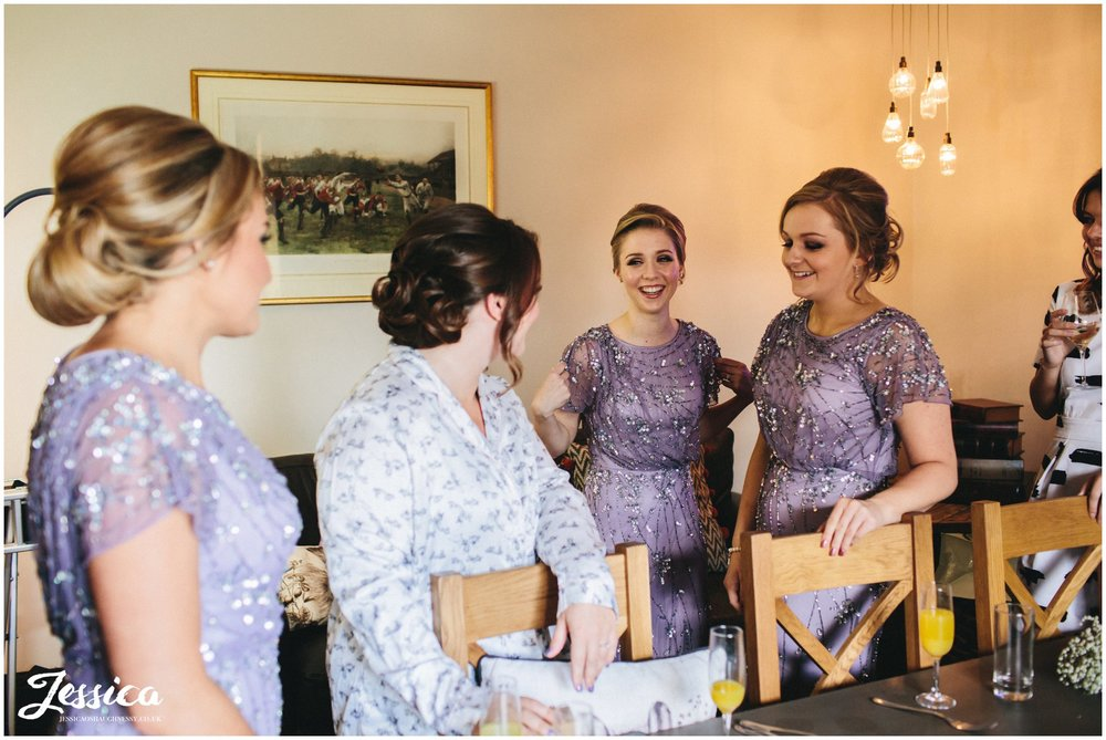 bridesmaids laugh with bride on her wedding morning in north wales