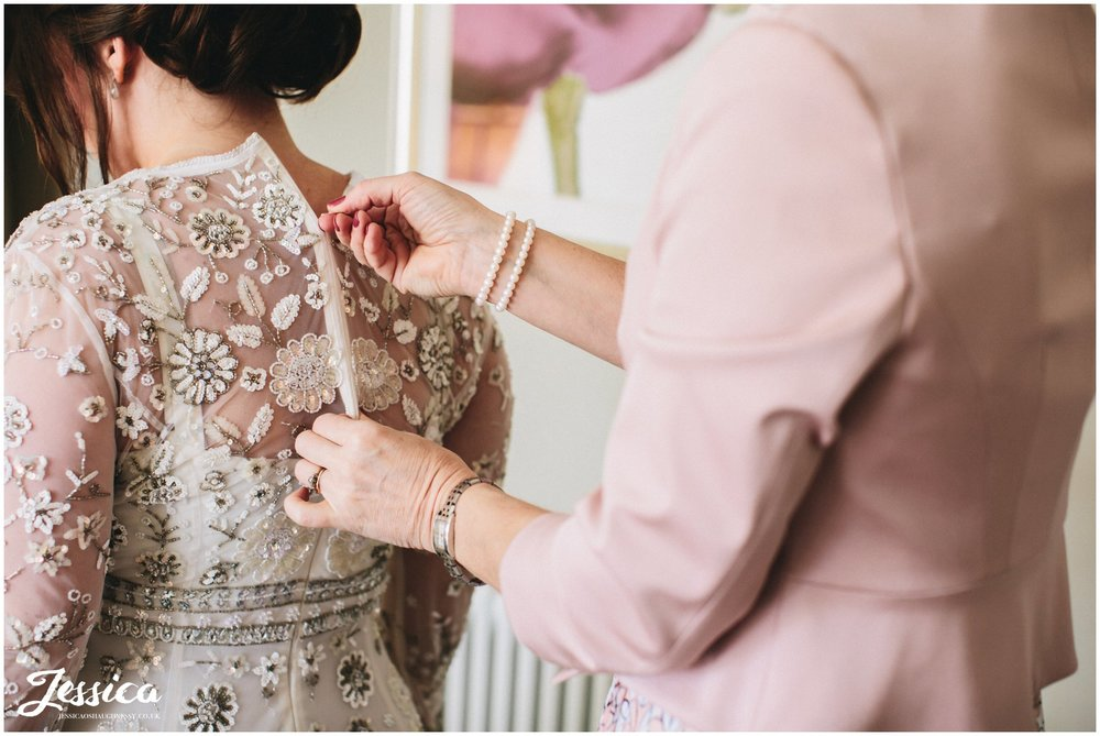 mother of the bride helping bride into her wedding dress
