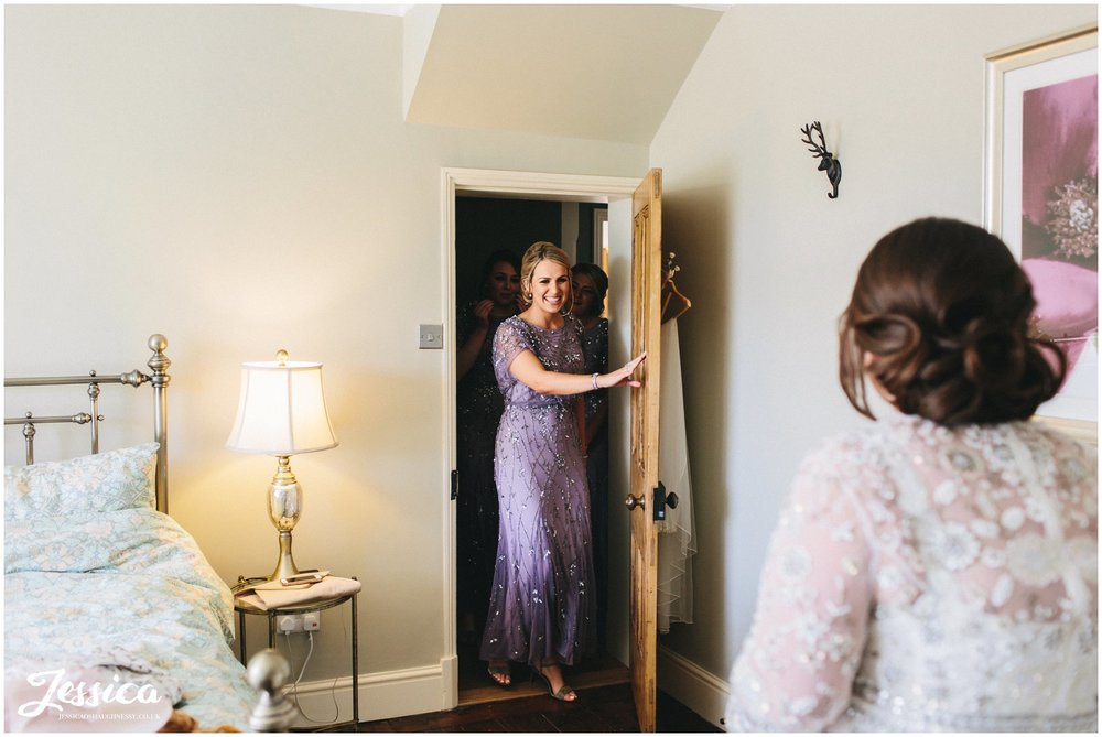 bridesmaids see the bride in her dress for the first time