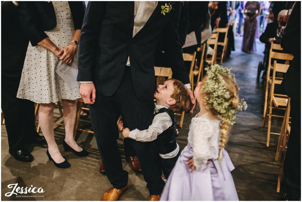 child hugs his dads legs after walking down the aisle