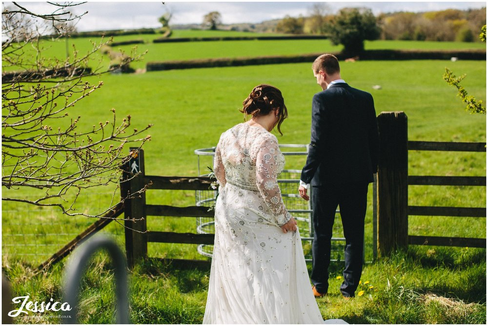 newly wed's walk through gates into field