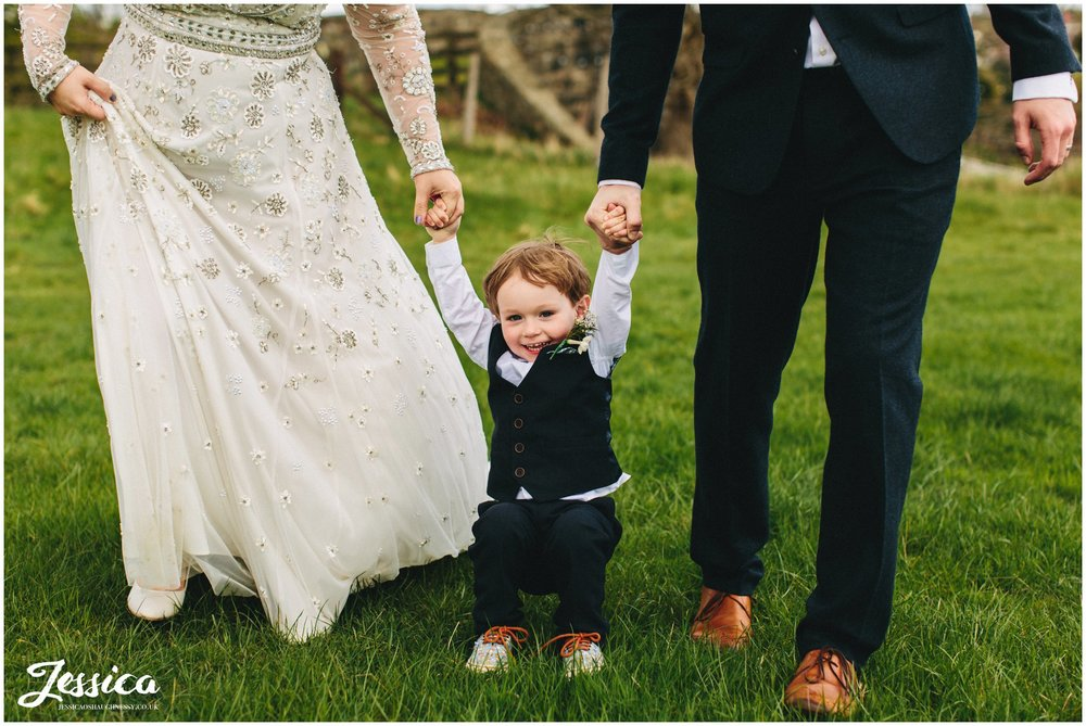 child holds parents hands at a wedding in trevor, wrexham