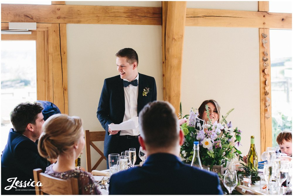 groom laughs whilst he gives his speech