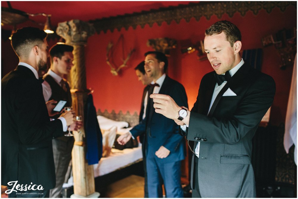 groom puts on watch before his wedding ceremony at trevor hall in north wales