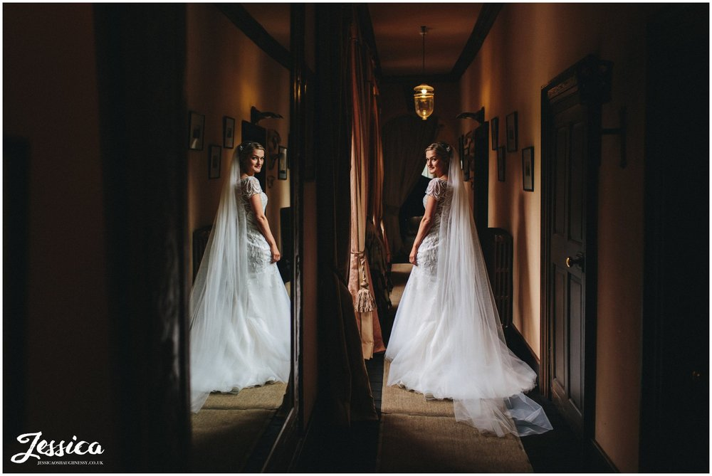 bride stands in coridoor of trevor hall, wreham