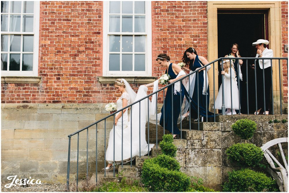 bridal party walk out of trevor hall to the ceremony