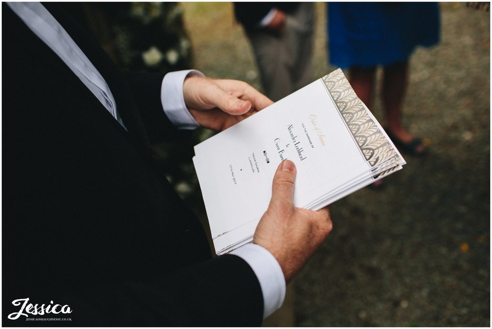 groomsman hands out order of service to wedding guests