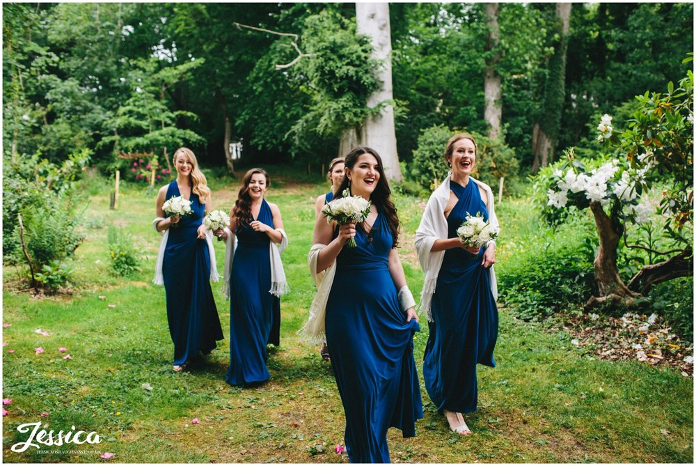 bridesmaids walk down grass path to trevor hall's church