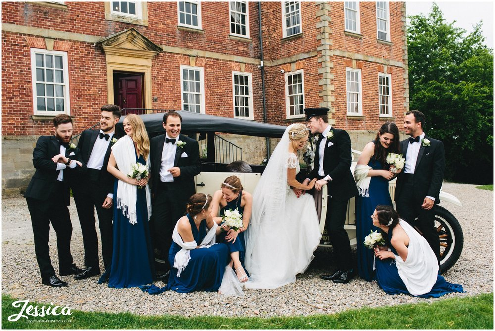 whole wedding party posing in from of the wedding car in north wales