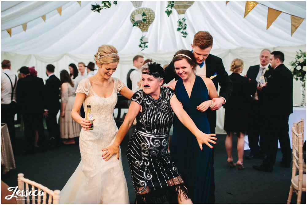 guest poses in 20's dress during a wedding in trevor hall