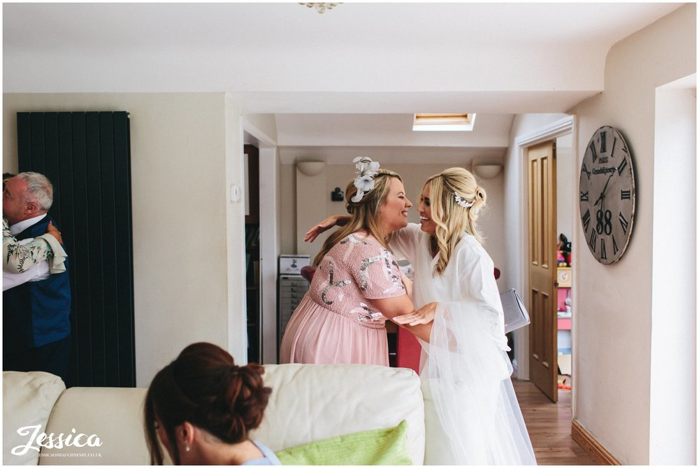 friend hugs bride on the morning of her wedding on the wirral