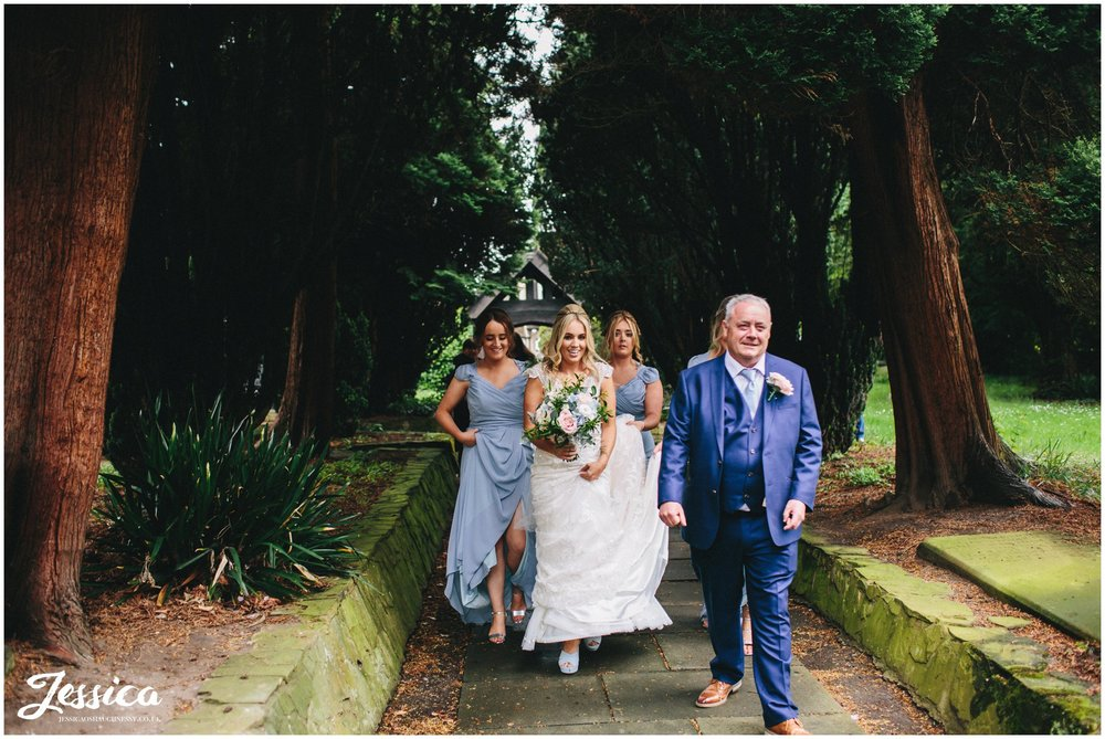 bride and bridesmaids walk down church path - wirral wedding