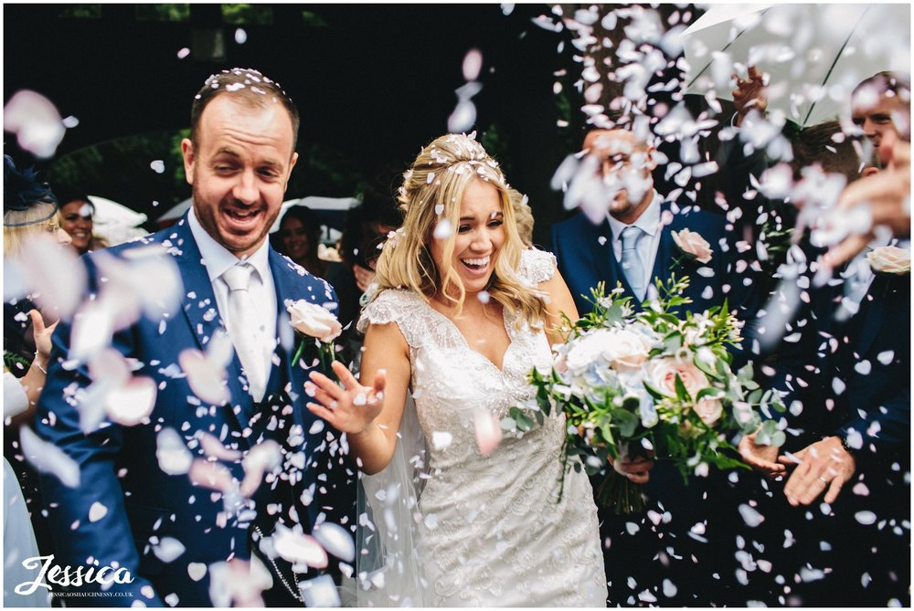 bride & groom walking through epic confetti line on their wirral wedding day