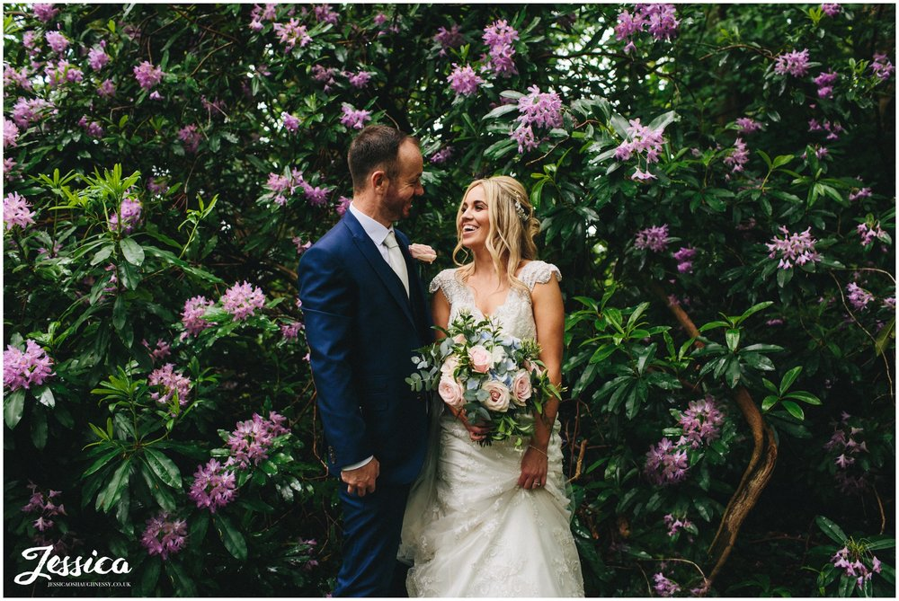 bride & groom surrounded by purple flowers on their wedding day at thornton manor