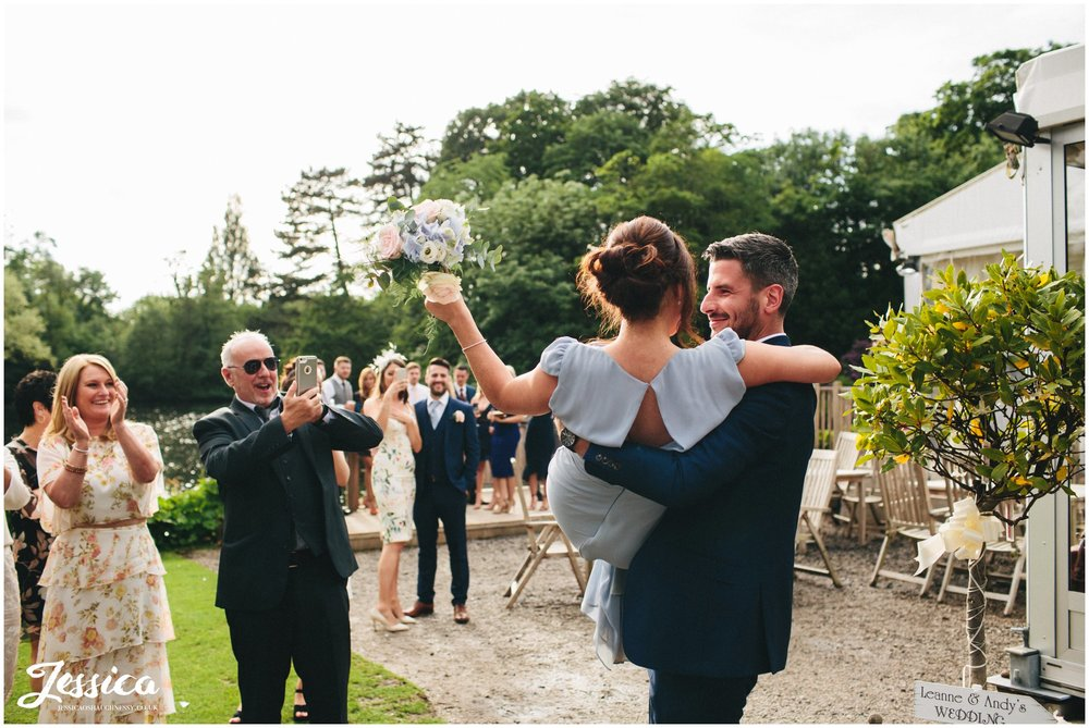 bridesmaid catches bouquet and is lifted up by her partner