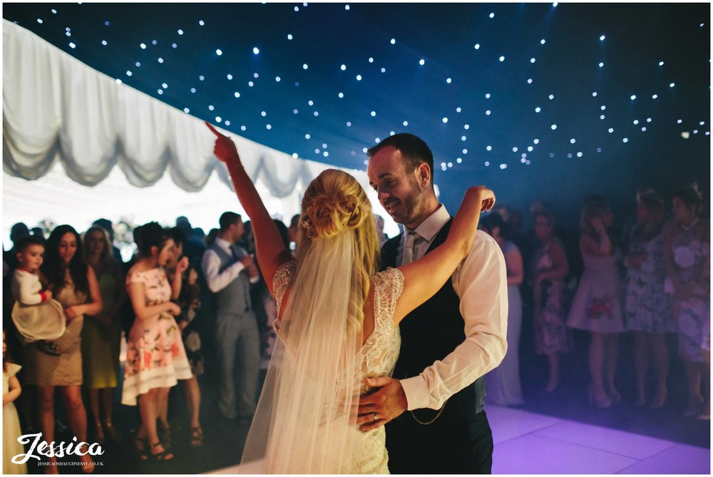 bride & groom share their first dance in the lakeside marquee - thornton manor