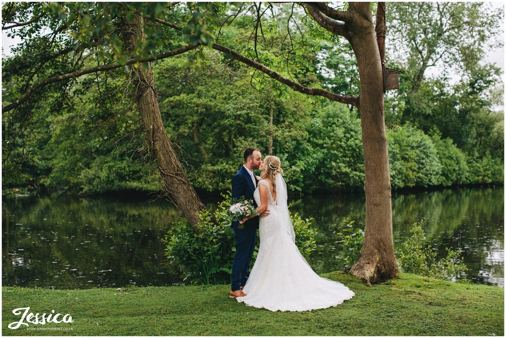 newly wed's kissing by the lake at thornton manor