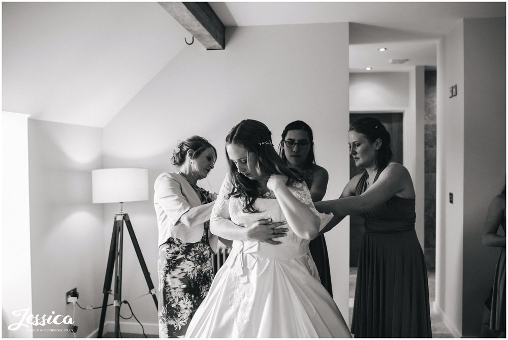 bride gets into her wedding dress in the bridal suite