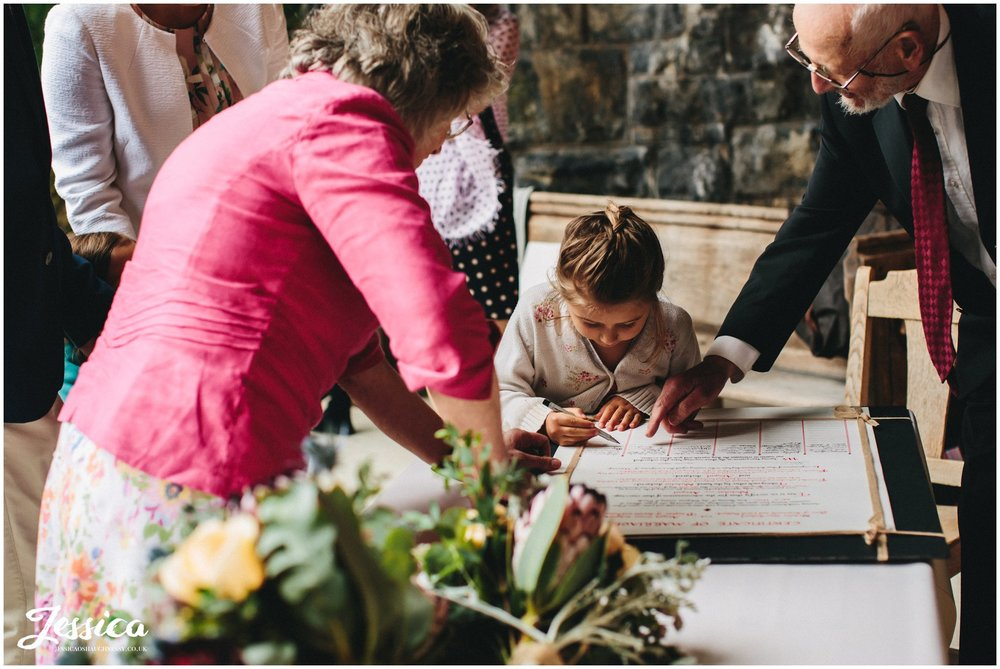 child signs quake wedding certificate under the bride at tower hill barns