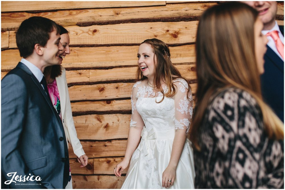 bride laughs with guests after her wedding ceremony