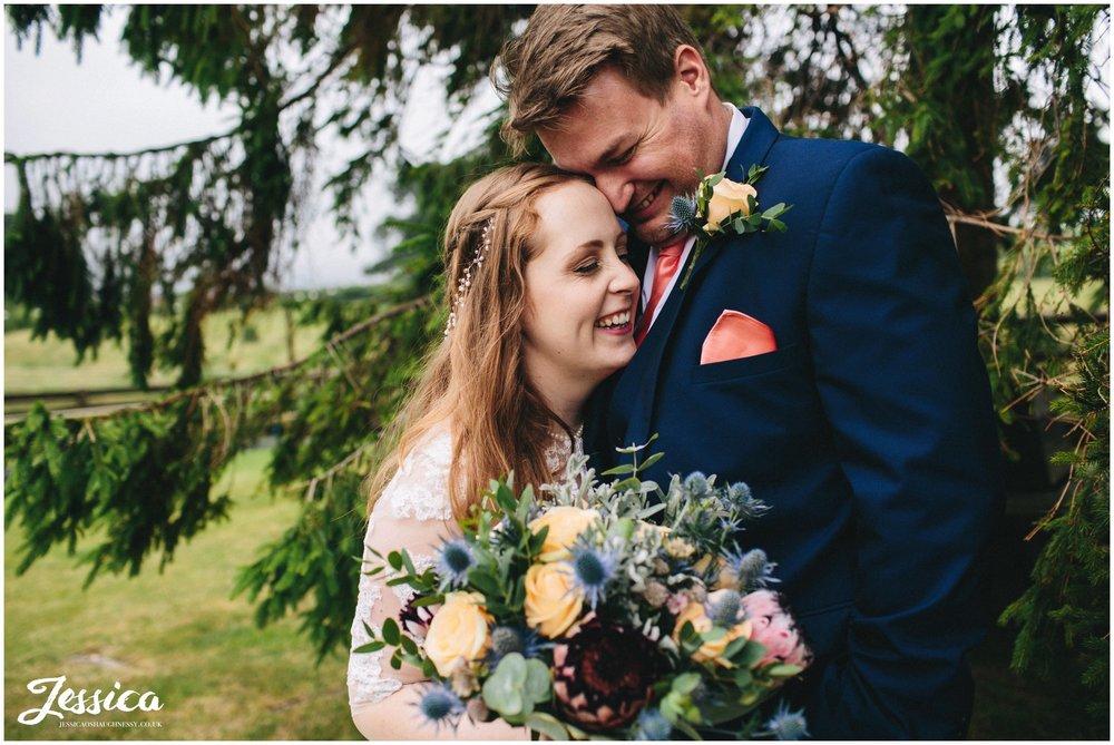 bride & groom hug laughing at tower hill barns - north wales wedding
