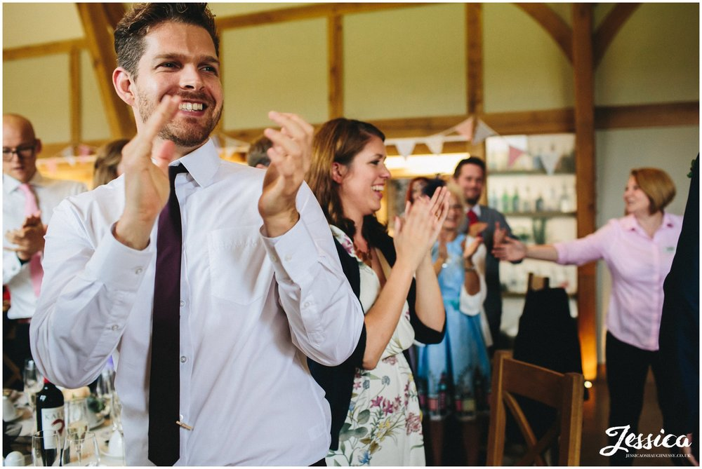 guests aplaude newly wed's as they enter the barn