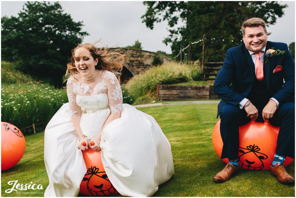 bride & groom bounce on space hoppers on their north wales wedding day