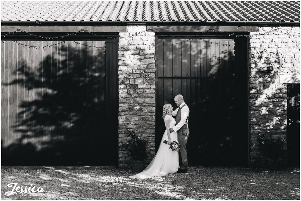 black and white photograph of bride and groom in front of barn doors