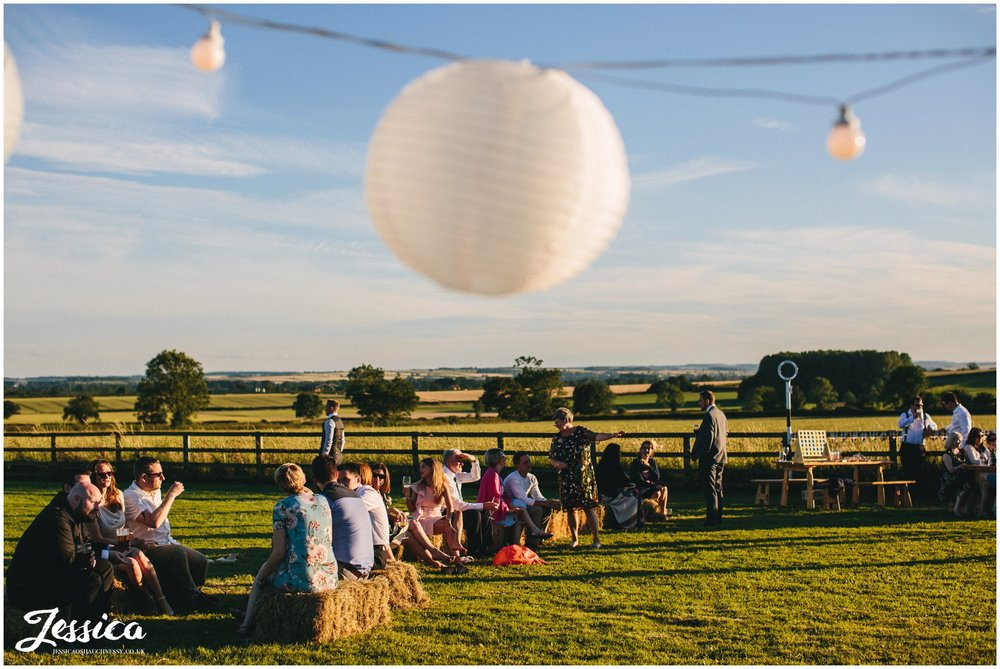 guests sitting on hay bails during the wedding celebrations