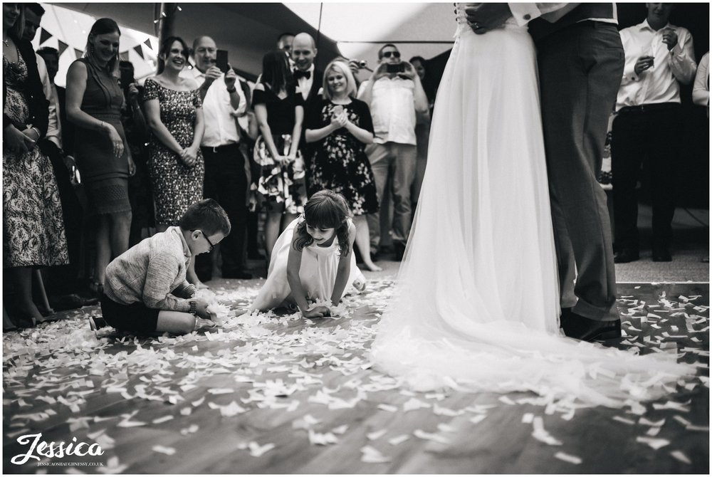 children gather up confetti to throw on the couple