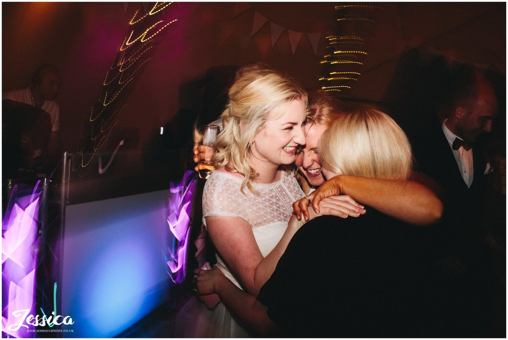 bride and friends hugging on the dancefloor - tipi wedding