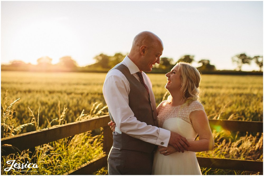 newly wed's hug in front of corn fields during golden hour