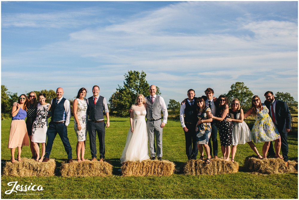 bride, groom and friends pose on hay bails - yorkshire wedding