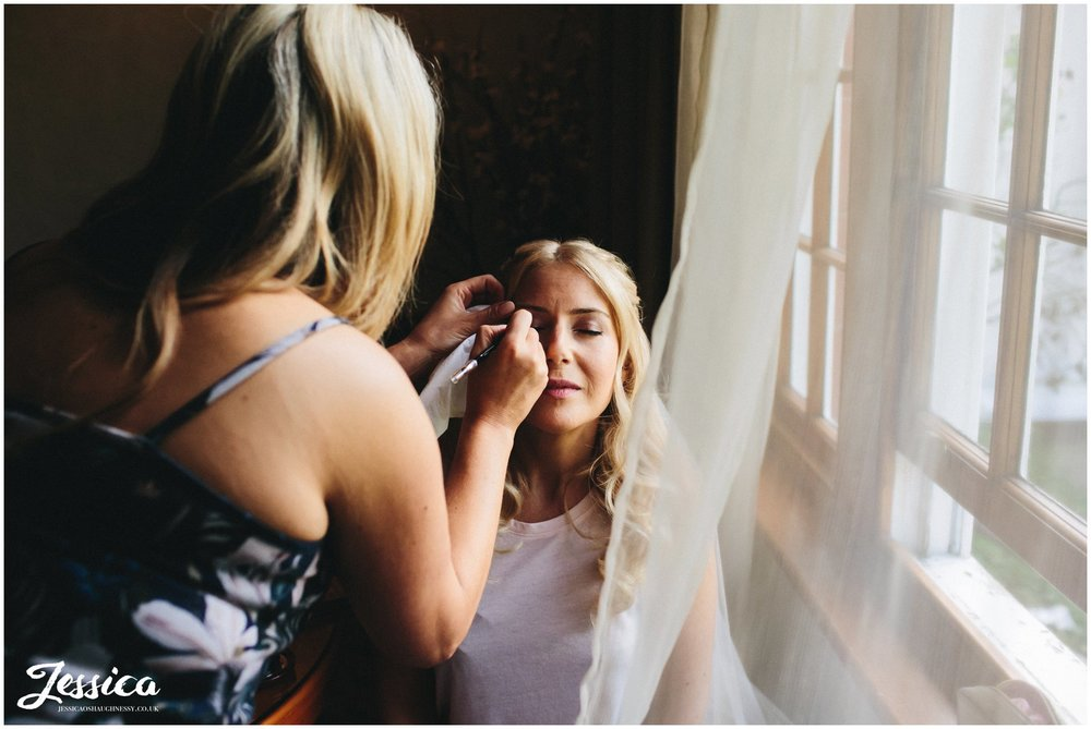 bride having her makeup done for her cheshire wedding
