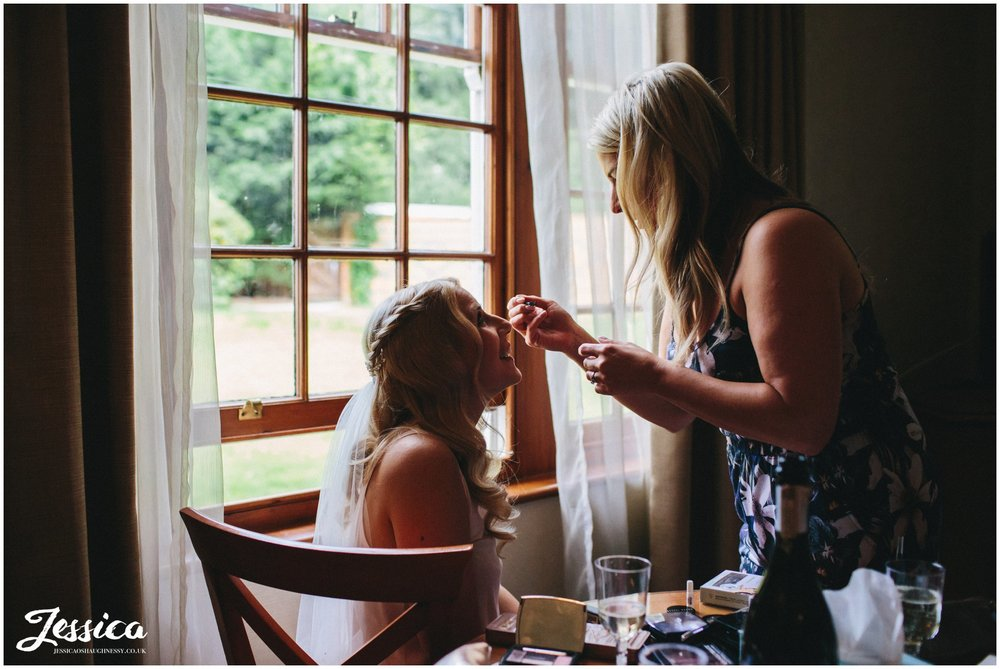 nunsmere hall in cheshire - bride gets makeup done