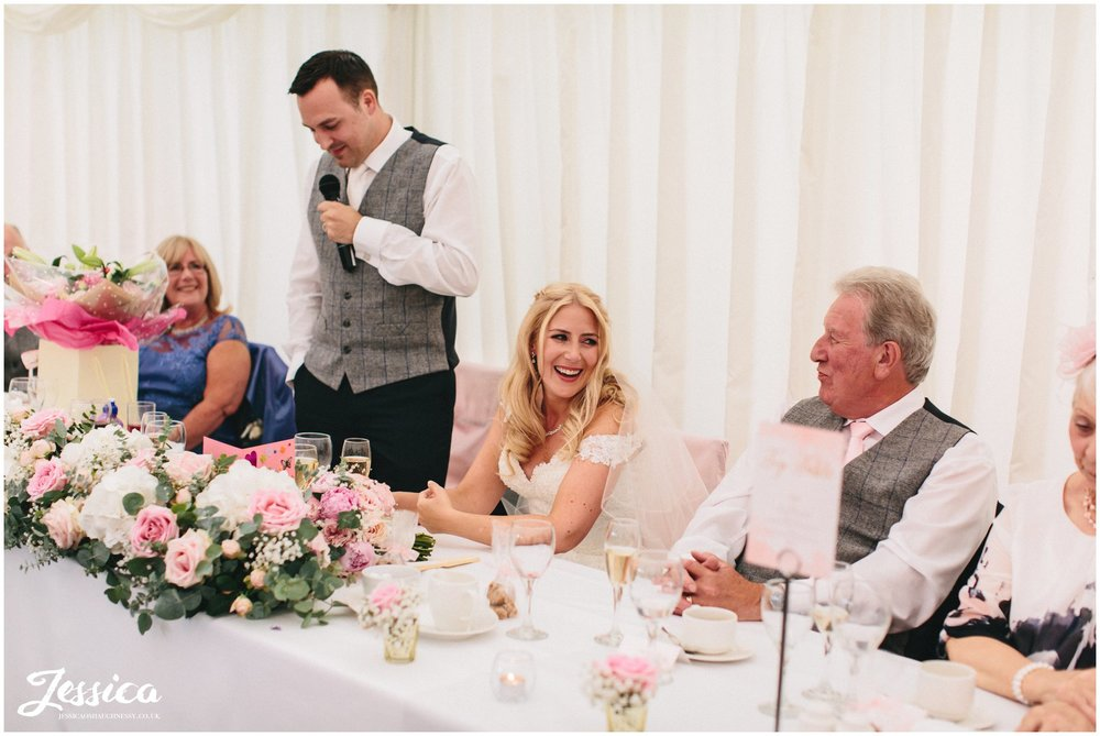 bride enjoying groom's speech at her wedding in nunsmere hall, cheshire