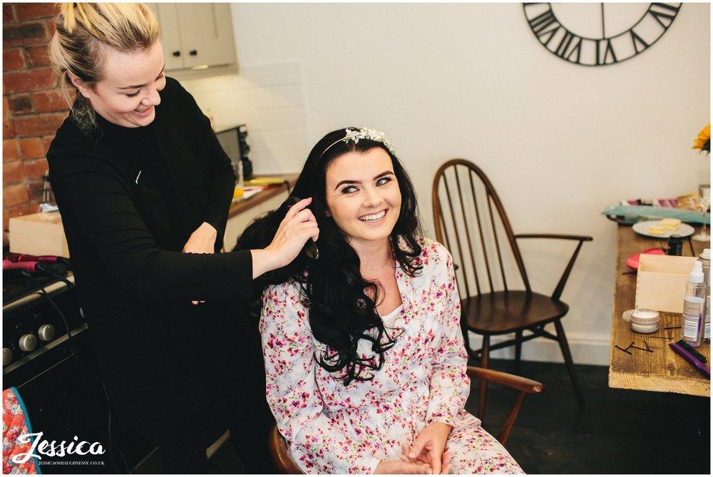 bride gets makeup done on her wedding morning