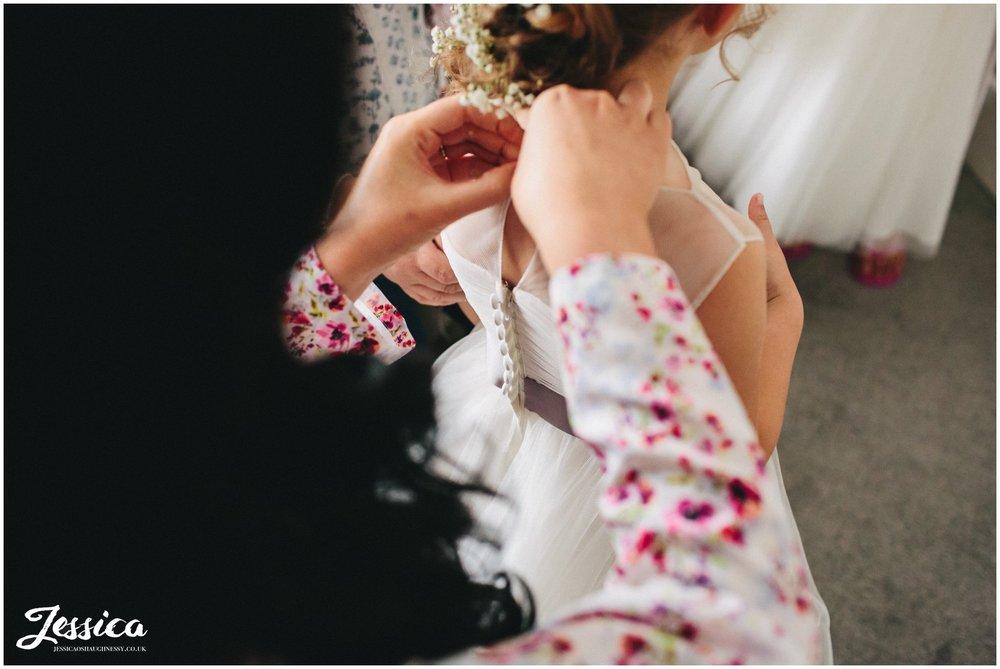 flower girl gets into her dress for the ness garden wedding