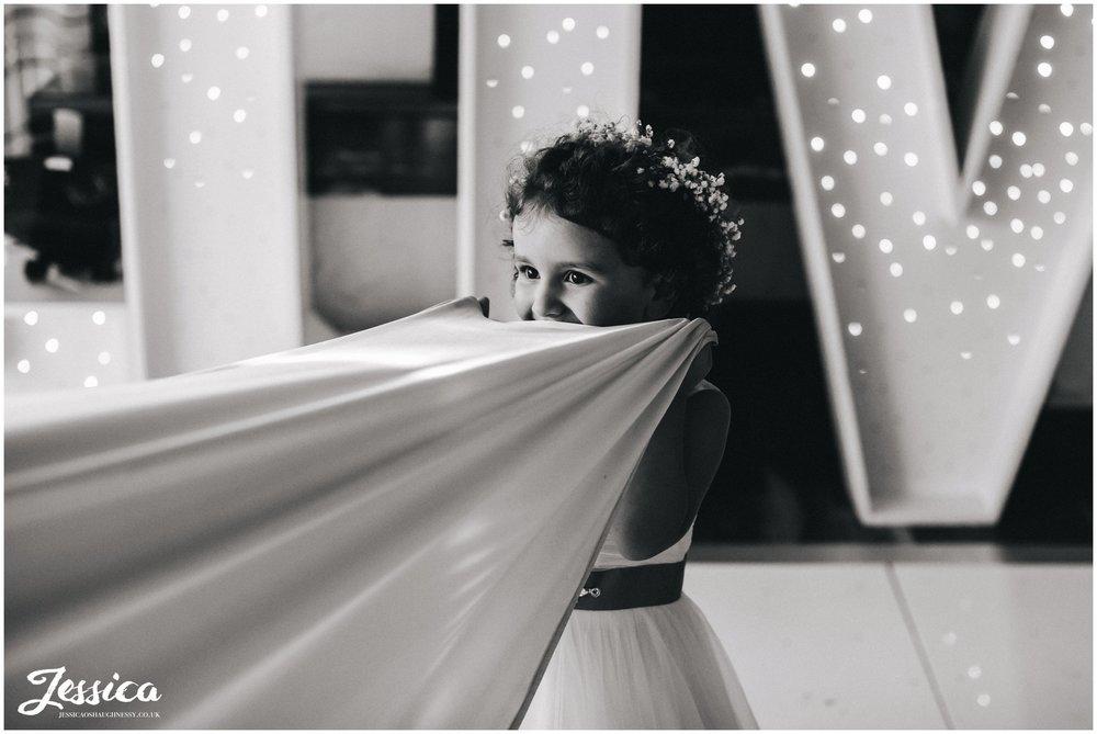 flower girl hides under brides dress