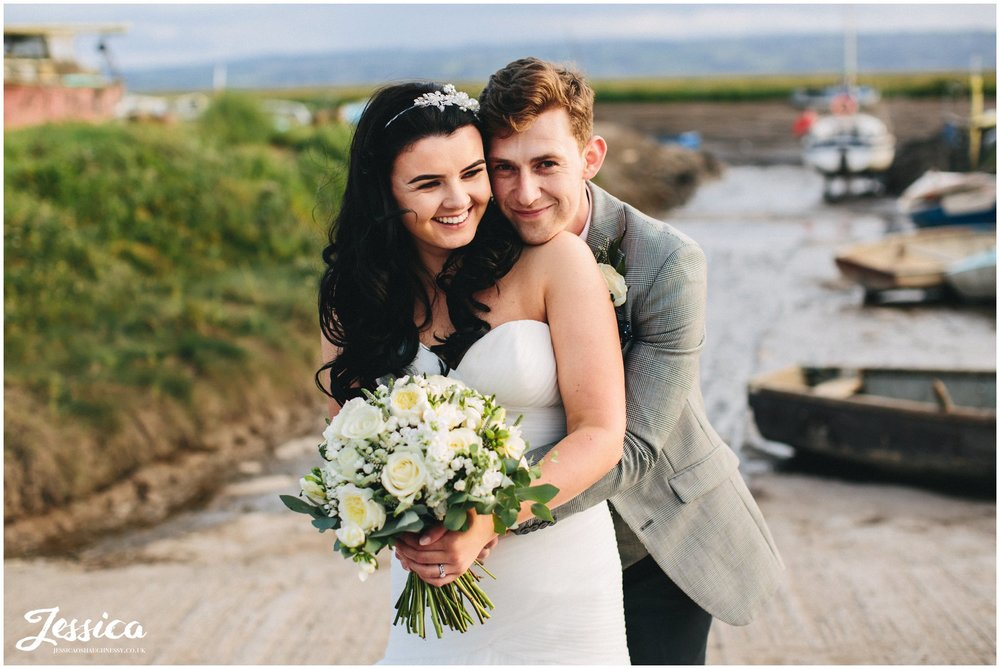 bride & groom embrace in front of the waterfront at sheldrakes restaurant