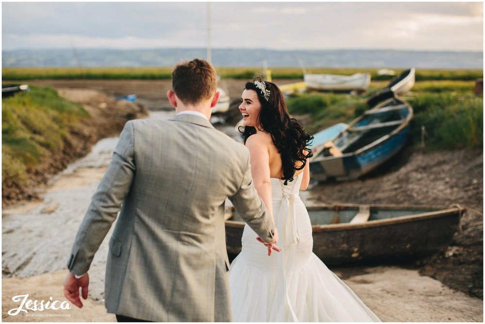 bride drags groom towards the water, wirral wedding photographer
