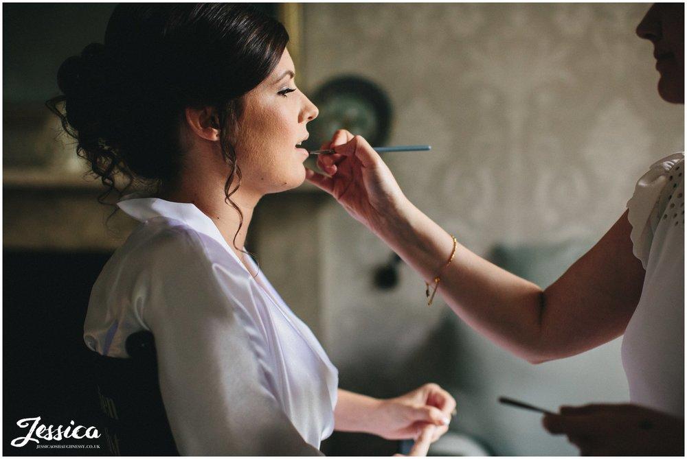 bride gets lipstick applied by make up artist