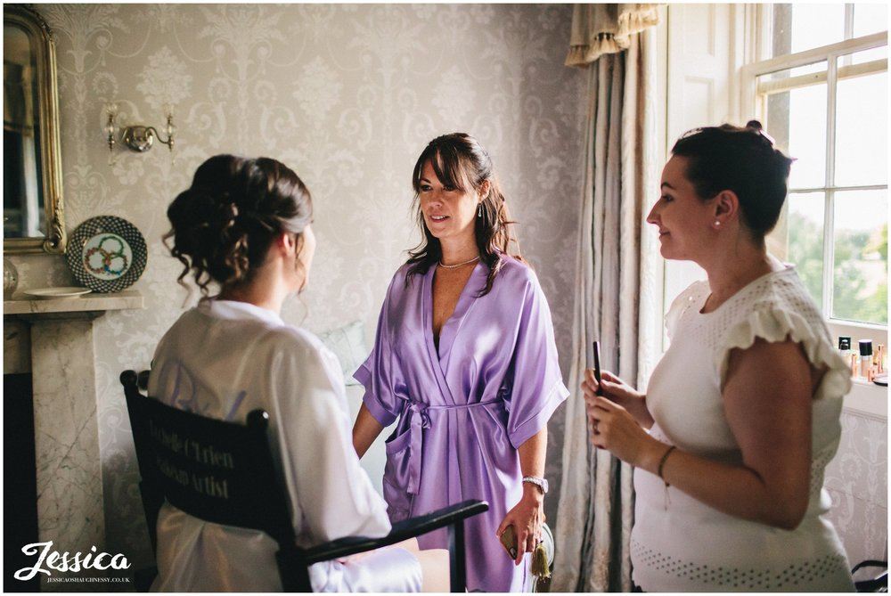 mother of the bride admiring brides makeup