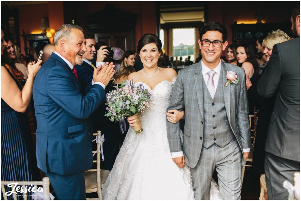 newly wed's exit their prestwold hall wedding ceremony