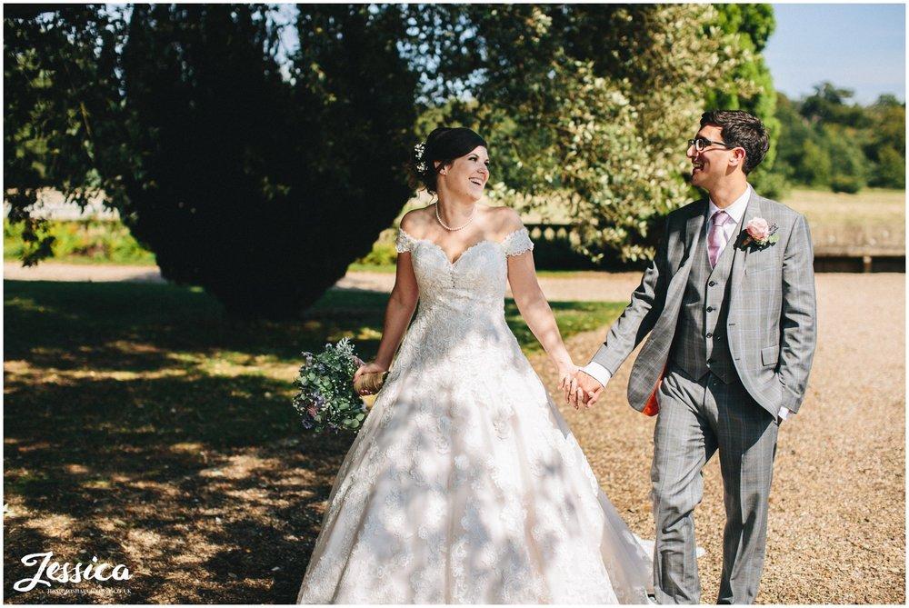 newly wed's walk hand in hand under tree's - prestwold hall wedding