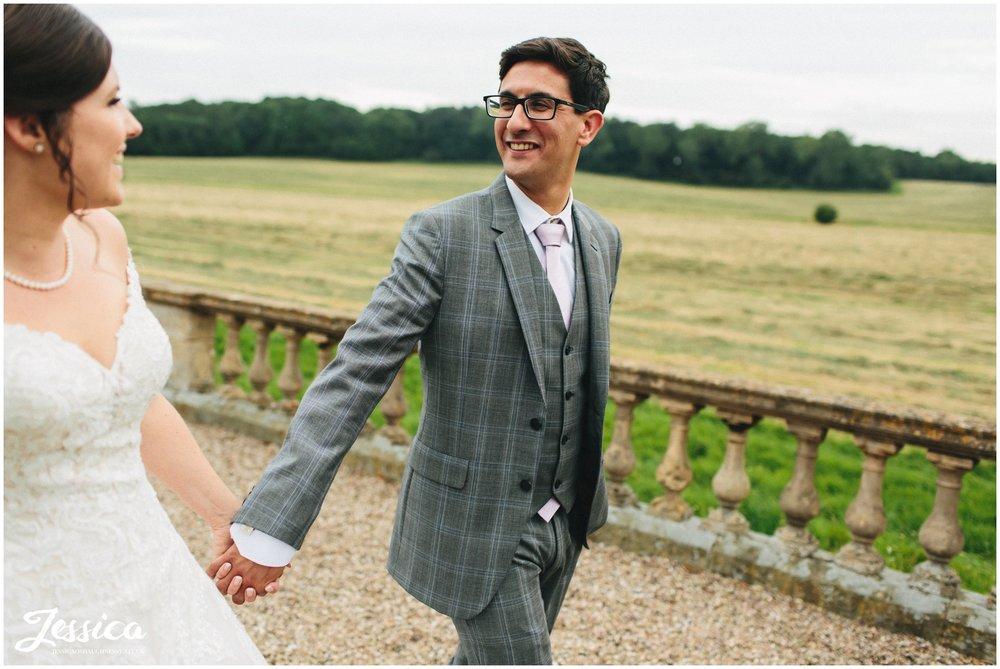 groom holds brides hands in prestwold halls grounds