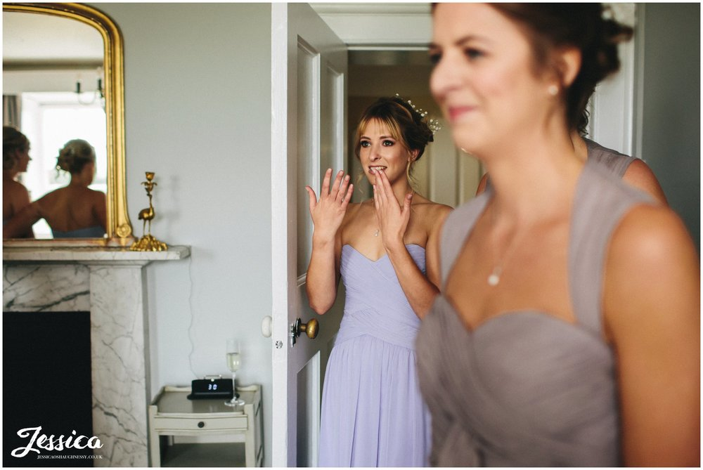 bridesmaid cries looking at bride in her dress