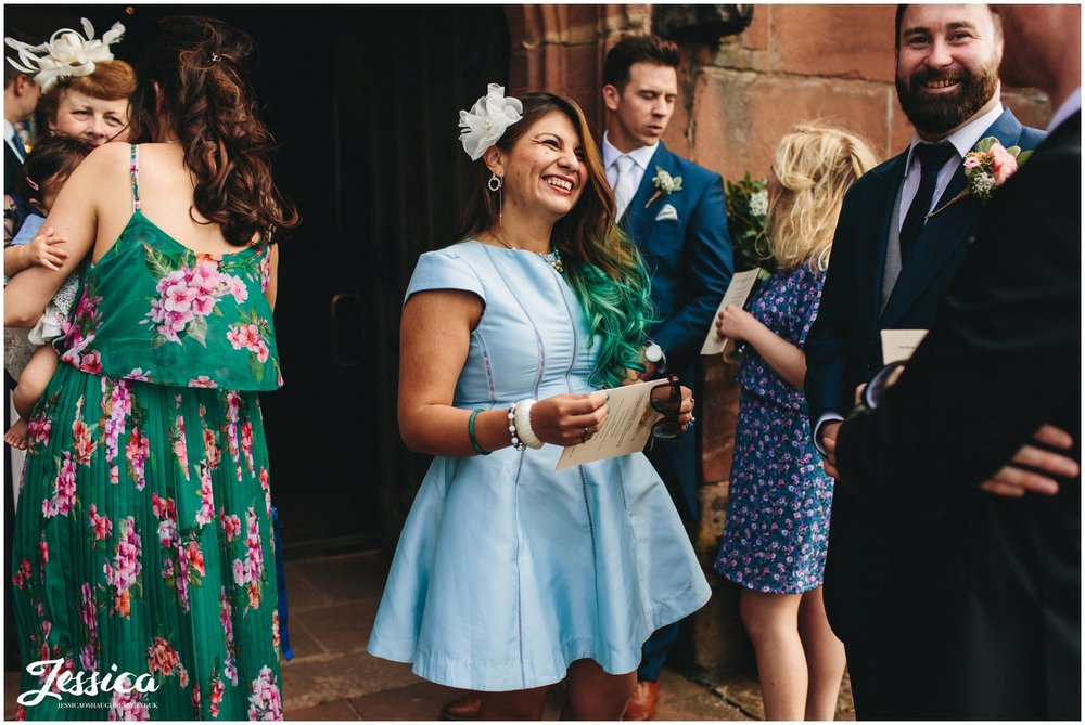 wedding guests laughing outside church