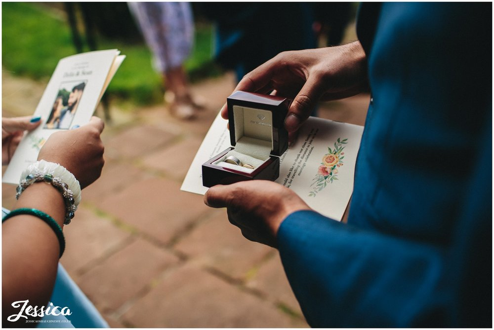 best man shows off wedding rings